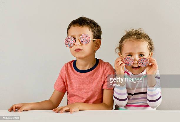 Boy and girl wearing sunglasses made of cookies covered in sprinkles