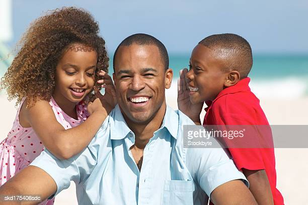boy (10-11) and girl (10-11) whispering to their father on the beach
