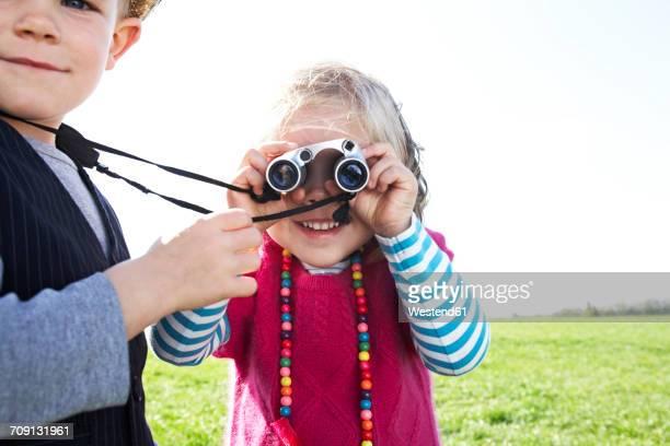 boy and girl with binoculars on meadow - curiosity stock-fotos und bilder