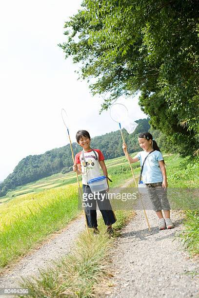Boy and girl with butterfly net, standing along the gravel path