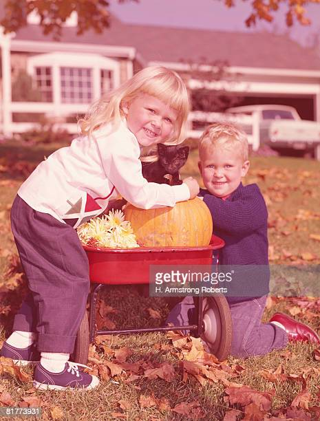 Boy and girl with kitten, flowers and pumpkin in wagon in backyard. (Photo by H. Armstrong Roberts/Retrofile/Getty Images)