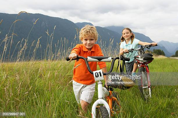 boy and girl (5-8 years) with mountain bikes in long grass, smiling, portrait - 6 7 years stock pictures, royalty-free photos & images