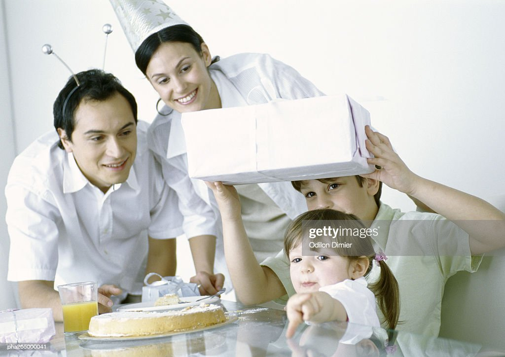 Boy and girl with parents having birthday party : Stockfoto