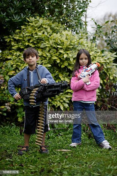 Boy and girl with toy guns in garden