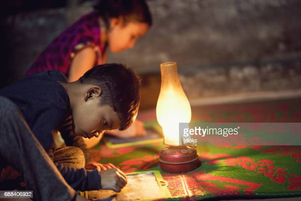 Boy and girl writing on slate under oil lamp