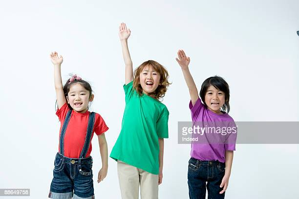 Boy and girls raising hands, smiling
