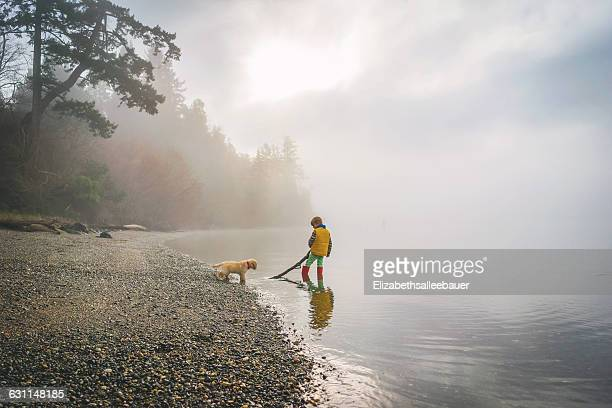 Boy and golden retriever puppy dog playing with stick in the ocean