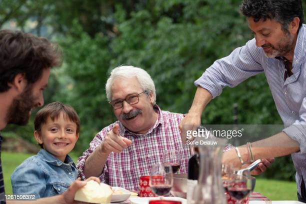 boy and grandfather at family meal - adulto di mezza età foto e immagini stock
