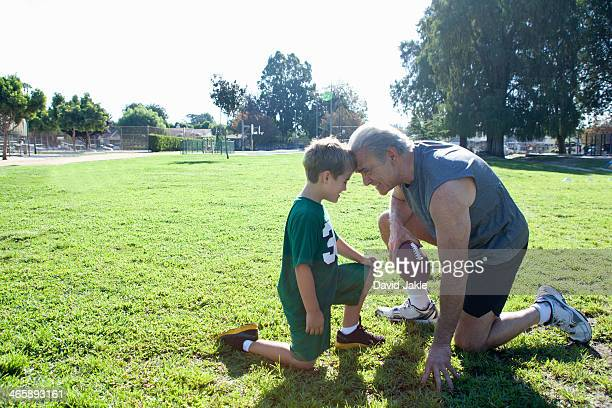 boy and grandfather head to head, man holding football - old american football stock photos and pictures