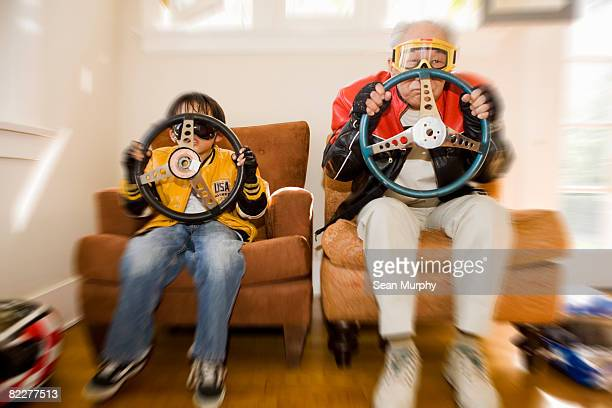 Boy and grandfather holding steering wheels