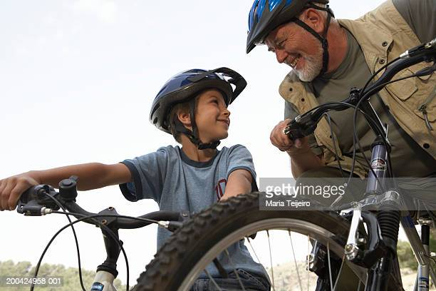 Boy (5-7) and grandfather on mountain bikes, smiling, low angle view