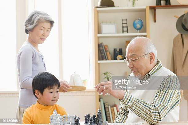 Boy and grandfather playing chess and grandmother carrying tea tray