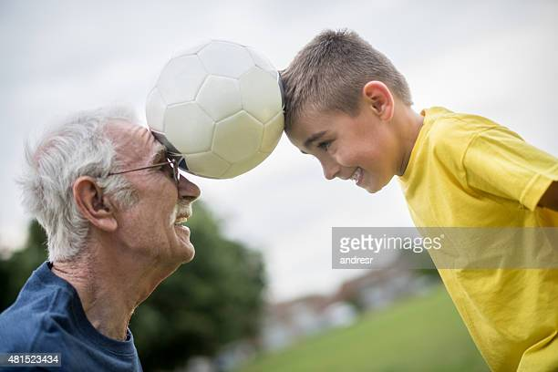 Boy and grandfather playing football together
