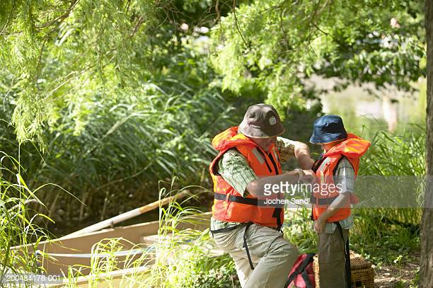 boy (6-8) and grandfather putting on life jackets at side of lake - life jacket stock pictures, royalty-free photos & images