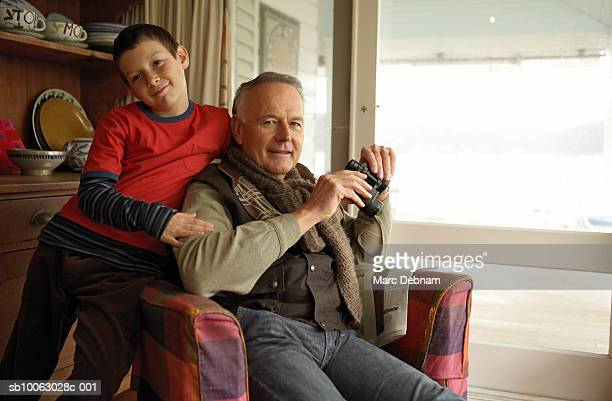 Boy (10-11) and grandfather sitting in armchair at home, portrait