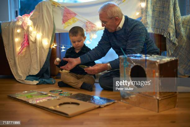 Boy and grandfather sitting on floor making robot costume