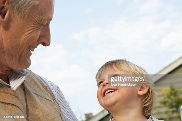 Boy (2-4 years) and grandfather smiling at eachother outdoors, close-up