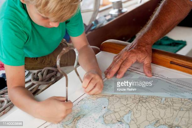 boy and grandfather using dividers on navigation maps in sailboat cabin - kartographie stock-fotos und bilder