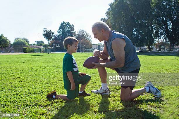 boy and grandfather with american football - pep talk stock pictures, royalty-free photos & images