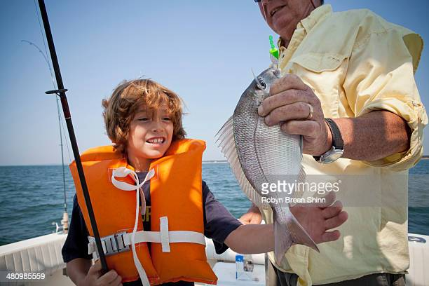 boy and grandfather with caught fish on boat, falmouth, massachusetts, usa - fish love stock photos and pictures