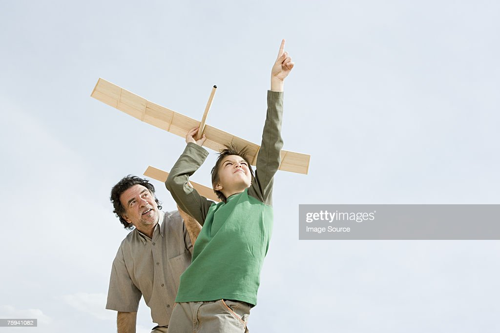 Boy and grandfather with toy aeroplane : Stock Photo