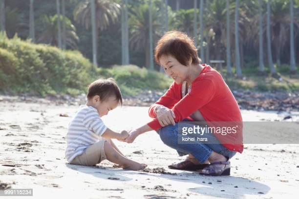 少年と祖母が海岸で遊んで