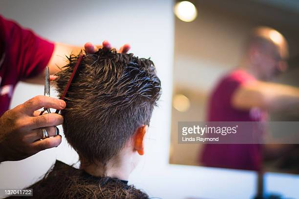 Boy and hairdresser at barber shop