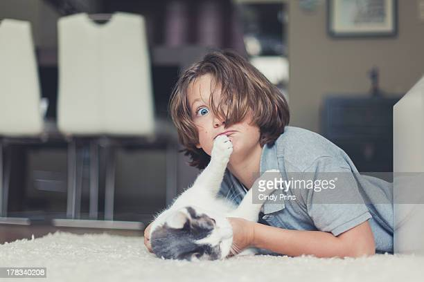 A boy and his cat playing on the floor