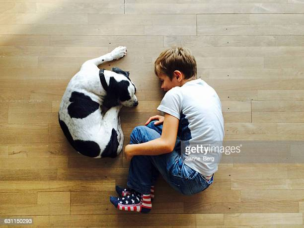 Boy and his dog curled up on the floor