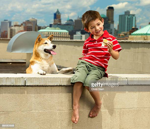 Boy and his dog eating hot dogs