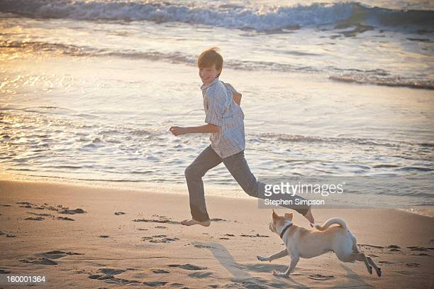 boy and his dog running on the beach