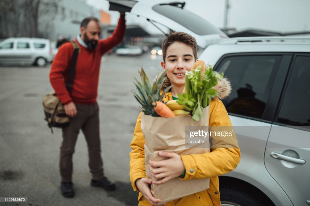 Boy and his father after grocery shopping : Stock Photo