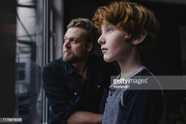 boy and his father looking out of window on rainy day - attendre photos et images de collection