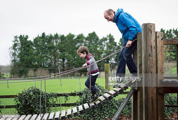 A boy and his father on a climbing frame, balancing on a gangway.