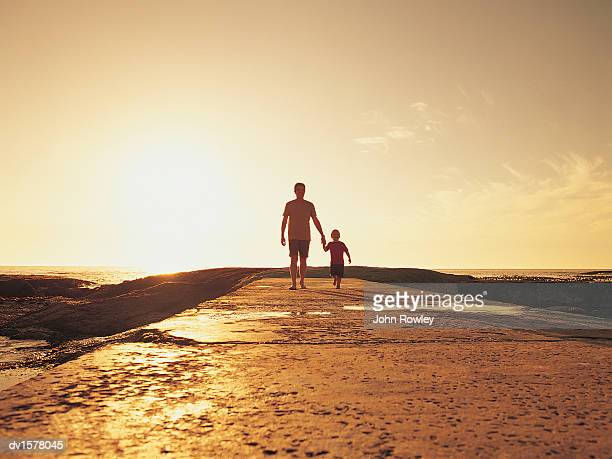 Boy and His Father Walking on the Beach in the Sunlight
