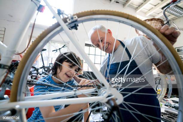 Boy and his grandfather adjusting the back wheel of a bicycle at the family business workshop