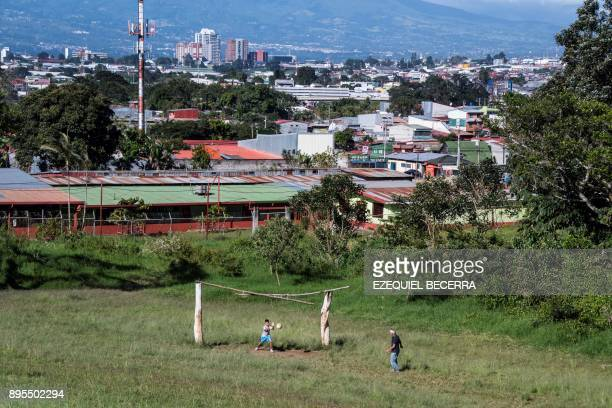 TOPSHOT A boy and his grandfather play football using as a framework the two trees on a soccer field in San Jose 19 December 2017 AFP PHOTO /...