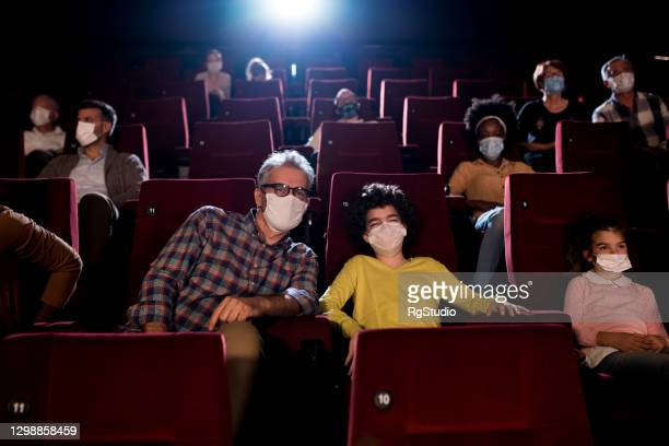 boy and his grandfather watching a movie at the cinema and wearing protective masks - film premiere stock pictures, royalty-free photos & images