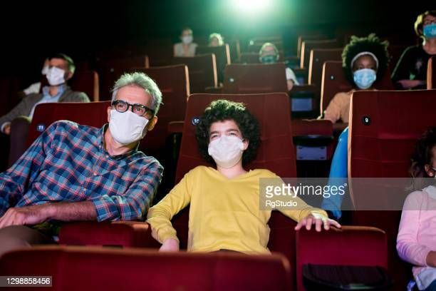 boy and his grandfather wearing face masks at the cinema - film premiere stock pictures, royalty-free photos & images