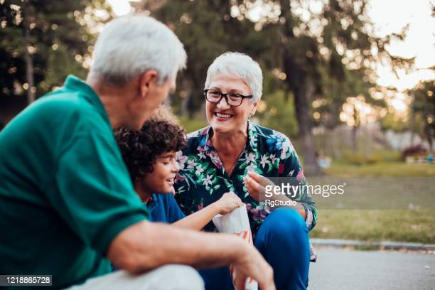 boy and his grandparents sitting in the park, eating popcorn and enjoying - human relationship stock pictures, royalty-free photos & images