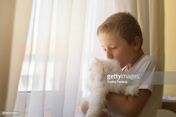 Boy And His Kitten Looking Though Window