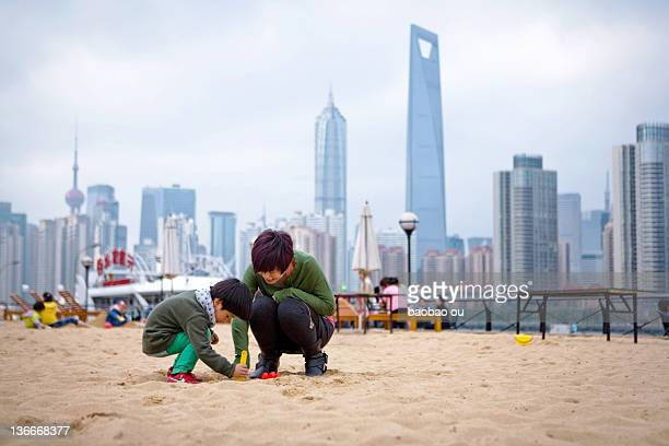 Boy and his mom playing on sands near bund