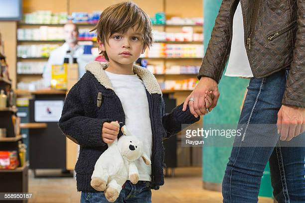Boy and his mother is looking for medical treatment in a pharmacy