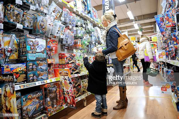 A boy and his mother look at toys as they buy Christmas gifts on December 15 2012 in a toy store in Lille northern France AFP PHOTO / PHILIPPE HUGUEN