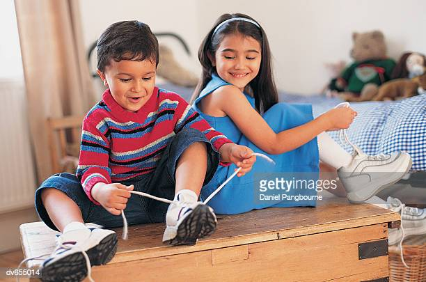 Boy and his Sister Putting Their Shoes on