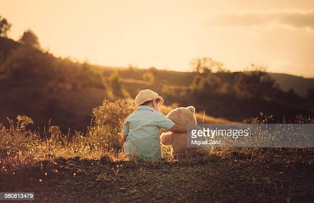 Boy and his teddy bear friend sitting on sunset