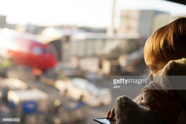 boy (4-5) and his teddy looking at airplane at airport, oslo, norway - toddler at airport stock pictures, royalty-free photos & images