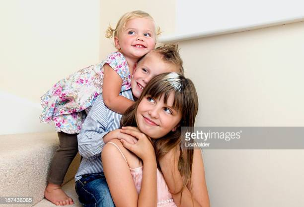 A boy and his two sisters cuddle in height order on stairs
