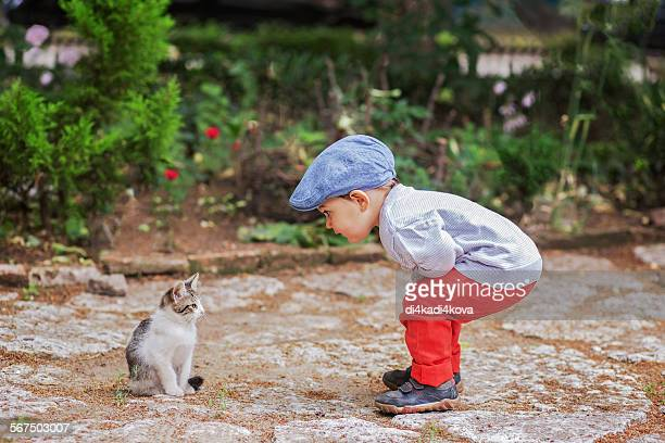 Boy and kitten looking at each other