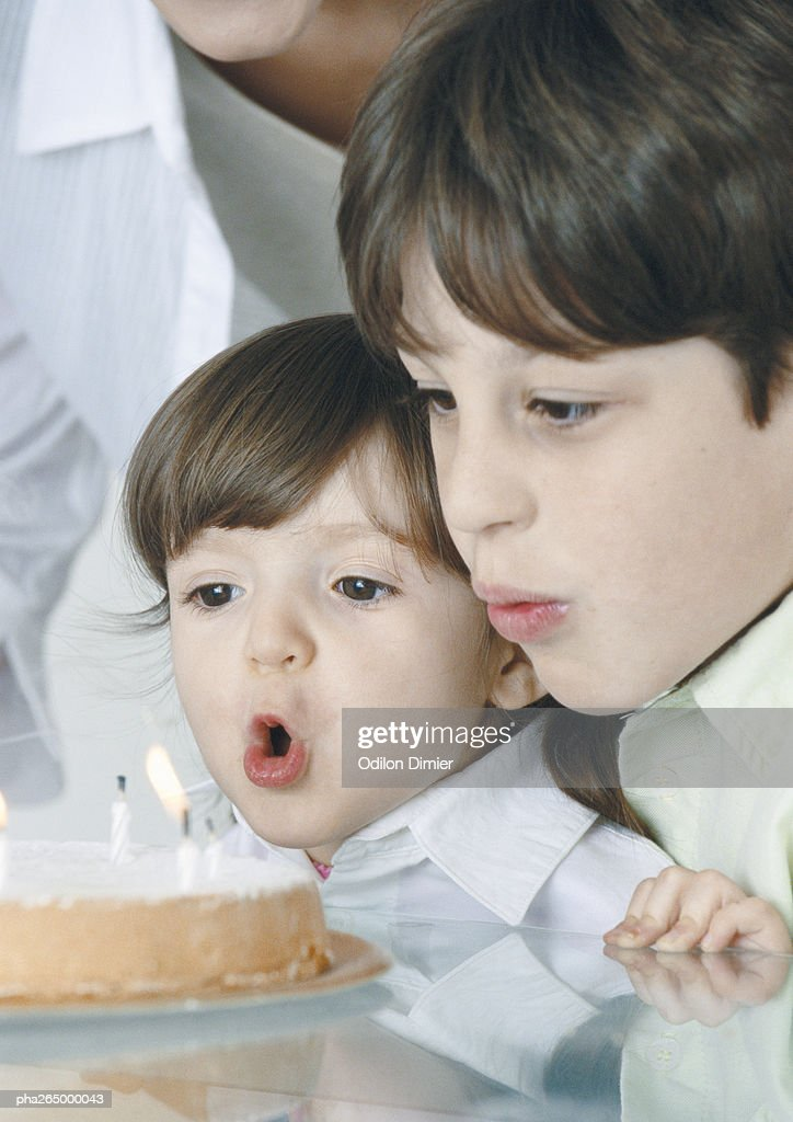 Boy and little girl blowing out candles on cake, mother in background : Stockfoto